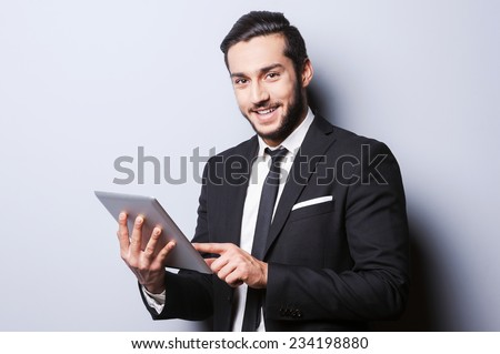 Confident and successful. Confident young man in formalwear working on digital tablet and smiling while standing against grey background - stock photo