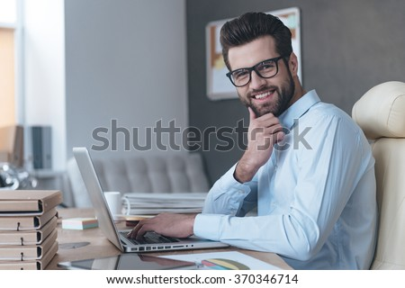 Confident and successful. Side view of handsome young man wearing glasses working with laptop and looking at camera with smile while sitting at his working place - stock photo
