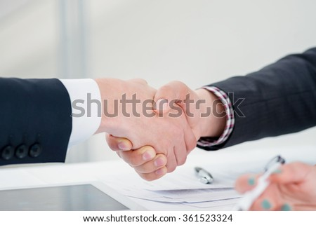 Confident and successful two businessmen shaking hands at the signing