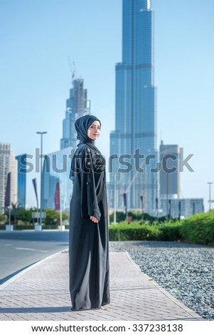 Confident Arab employee. Arab Business vumen in hijab is the street on the background of skyscrapers of Dubai. The woman is dressed in a black abaya - stock photo
