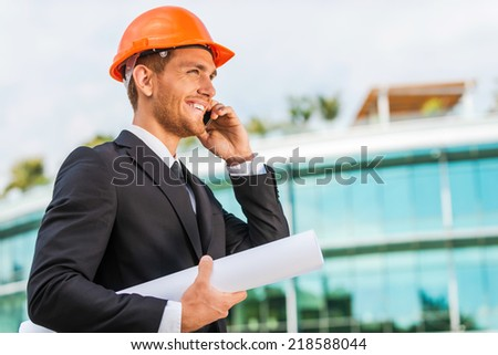 Confident architect. Handsome young man in hardhat holding blueprint and talking on the mobile phone while standing outdoors and against building structure - stock photo