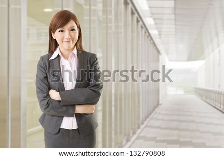 Confident Asian business woman stand in front of office buildings. - stock photo