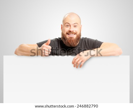 Confident at success. Happy bearded man showing thumb up and leaning at copy space while standing against grey background - stock photo