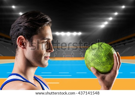 Confident athlete man holding a ball against handball field indoor