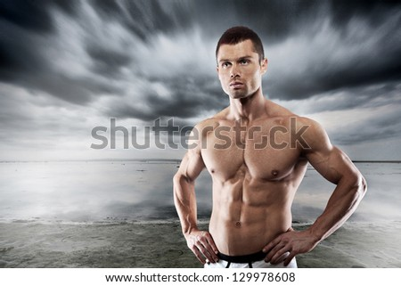 Confident athletic man against dramatic sky - stock photo