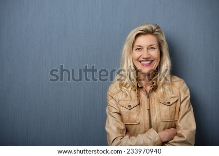 Confident attractive blond middle-aged woman with folded arms standing in front of a blank blackboard smiling happily at the camera with copyspace - stock photo