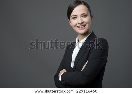 Confident attractive business woman with arms crossed posing on gray background. - stock photo