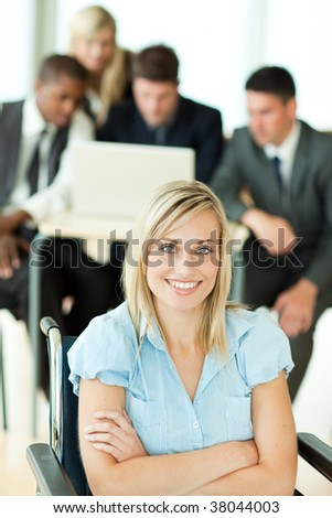 Confident attractive businesswoman with her group working in the background