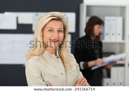 Confident attractive middle-aged businesswoman standing in her office with folded arms smiling at the camera as a colleague works in the background - stock photo