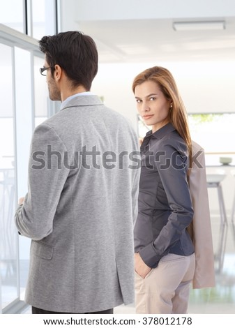 Confident attractive young blonde caucasian businesswoman with colleague at office, wearing suit, looking back at camera, hand in pocket, jacket on back, standing . - stock photo