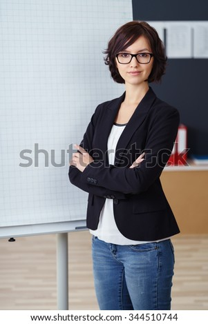 Confident attractive young businesswoman giving a presentation standing with folded arms alongside a flip chart with blank graph paper visible for your text or diagram - stock photo