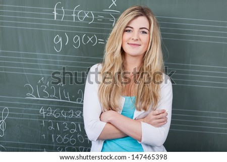 Confident attractive young female student in maths class standing with folded arms in front of the blackboard