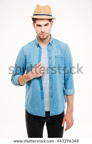 Confident attractive young man in blue shirt and hat standing over white background - stock photo