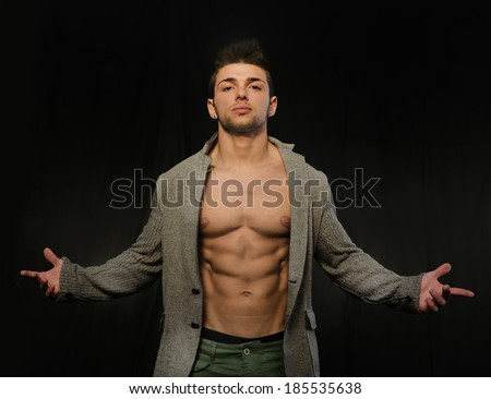 Confident, attractive young man with open jacket on muscular torso, ripped abs and pecs. Arms open - stock photo