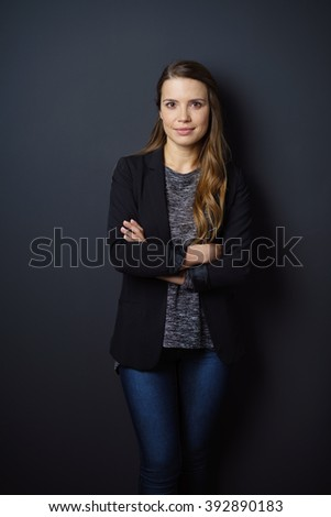 Confident attractive young woman in jeans with folded arms standing against a dark studio background looking at the camera with a quiet friendly smile