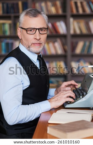 Confident author. Side view of confident grey hair senior man in formalwear sitting at the typewriter and looking at camera with bookshelf in the background - stock photo