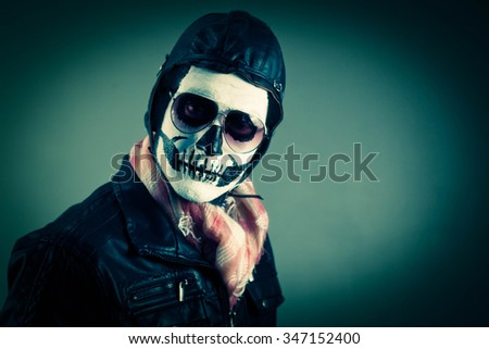 Confident aviator with face painted as a human skull - stock photo