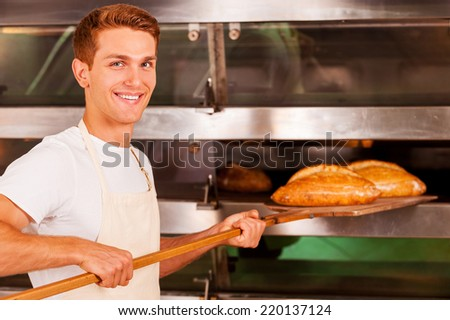 Confident baker. Confident young man in apron taking fresh baked bread from oven and smiling  - stock photo