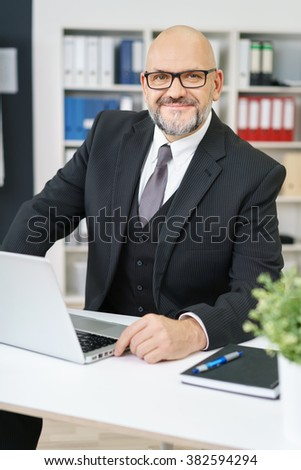 Confident balding senior businessman with a beard seated at his desk in the office smiling at the camera - stock photo