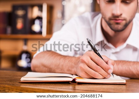 Confident bar owner. Close-up of handsome young male bartender in white shirt leaning at the bar counter and writing something in note pad - stock photo