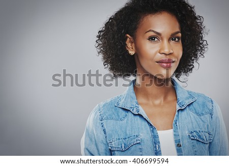 Confident beautiful black woman with blue jean shirt on gray background