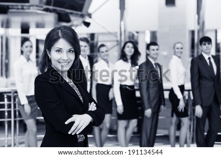 Confident beautiful female team leader sitting in a business meeting at a table with a group of her colleagues turning to smile at the camera, selective focus. Black and white. - stock photo