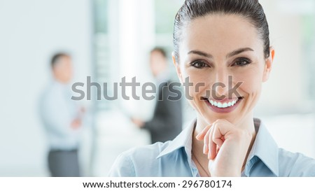 Confident beautiful smiling business woman in the office posing with hand on chin and looking at camera, office interior and business team on background, selective focus - stock photo