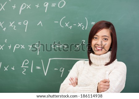 Confident beautiful young Asian teacher or student standing in front of a blackboard covered in mathematical equations smiling at the camera - stock photo