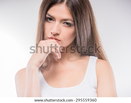 Confident beauty. Attractive young brunette woman posing against white background. - stock photo