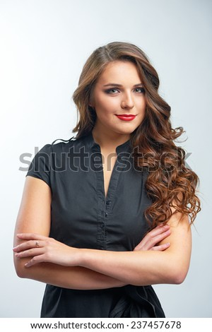 Confident beauty. Attractive young caucasian woman in black blouse standing with arms crossed over white background looking at camera - stock photo