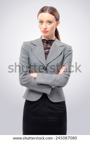 Confident beauty. Beautiful young business woman looking at camera and keeping arms crossed while standing isolated on grey. - stock photo