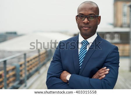 Confident black business man in a stylish suit standing with folded arms on a rooftop of n office block looking at the camera with a serious expression - stock photo