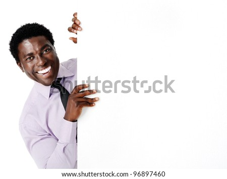 confident black businessman laughing and holding onto a blank advertising board - stock photo