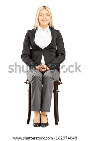 Confident blond businesswoman in suit sitting on a wooden chair isolated on white background - stock photo