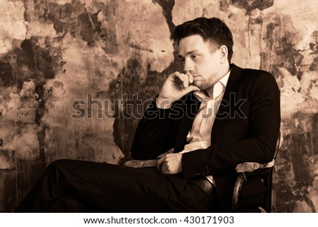 Confident blonde man in formal suit sits on an vintage chair