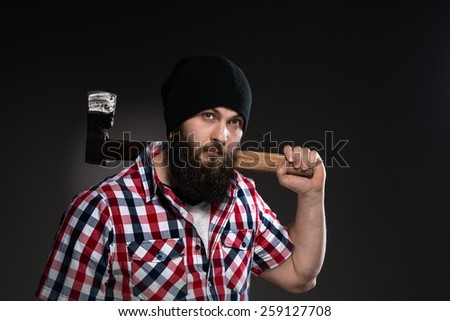 Confident, brutal bearded man with axe on a grey background. - stock photo