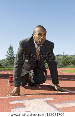 Confident business competitor at starting position of a race track - stock photo