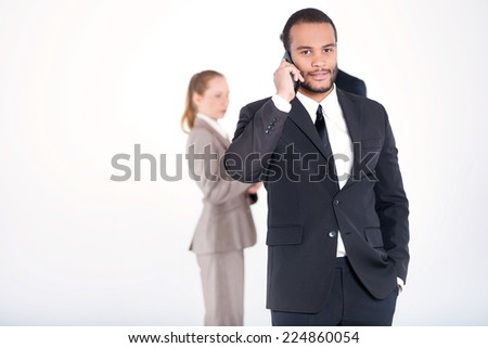 Confident business conversation. Successful and smiling African businessman talking on cell phone while his colleagues are working on a tablet in the background on a gray background - stock photo