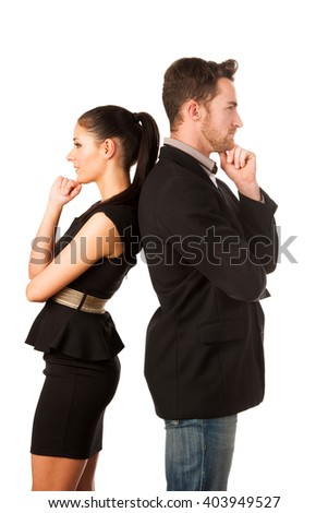 Confident business couple leaning on each other with backs, holding chin and thinking. Conceptual image.