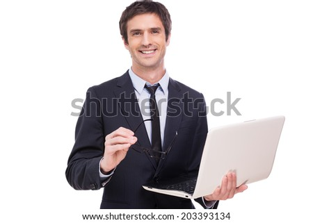 Confident business expert. Cheerful young man in formalwear holding laptop and smiling while standing isolated on white background - stock photo