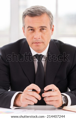 Confident business expert. Confident mature man in formalwear looking at camera while sitting at his working place - stock photo