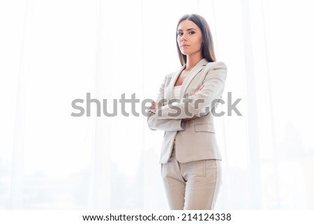 Confident business expert. Confident young businesswoman in suit keeping arms crossed and looking at camera  - stock photo