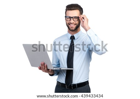 Confident business expert. Confident young handsome man in shirt and tie holding laptop and smiling while standing against white background - stock photo