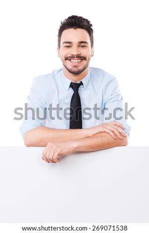 Confident business expert. Handsome young man in shirt and tie leaning at the copy space and keeping arms crossed while standing against white background - stock photo