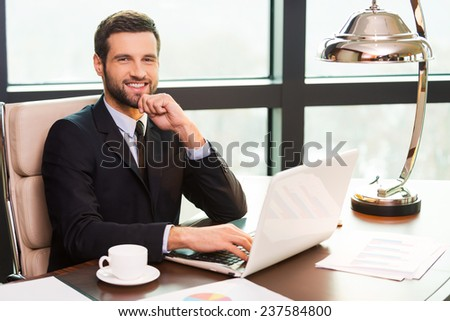 Confident business expert. Handsome young man in suit holding hand on chin and smiling while sitting at his working place - stock photo