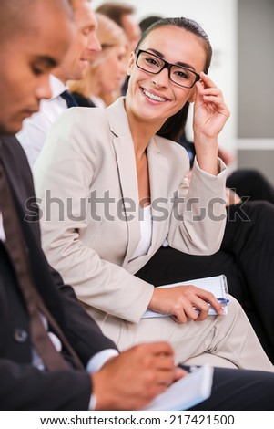 Confident business expert. Side view of business people sitting in a row and writing something in their note pads while confident young woman adjusting her eyeglasses and smiling - stock photo