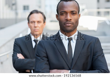 Confident business experts. Confident African man in formal wear keeping arms crossed and looking at camera while mature businessman standing behind him - stock photo