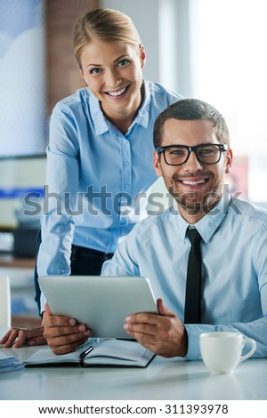 Confident business experts. Two cheerful young people in formalwear smiling and looking at camera while working together - stock photo