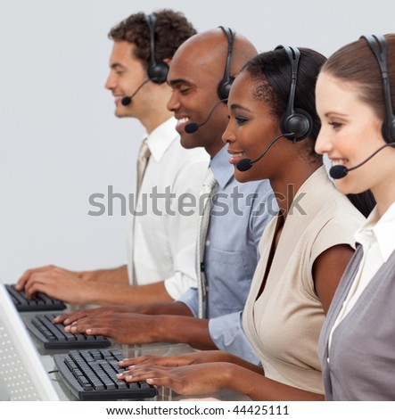 Confident business group in a line working at computers in the office