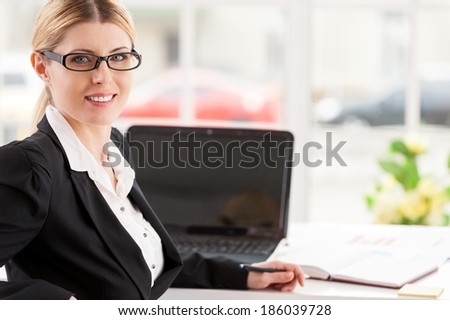 Confident business lady. Beautiful mature woman in formalwear looking over shoulder and smiling while sitting at her working place